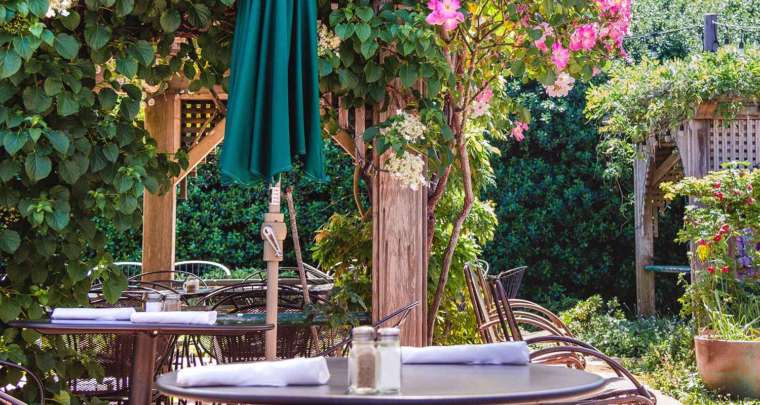 Outdoor seating on the garden patio, with lush plants and flowers.