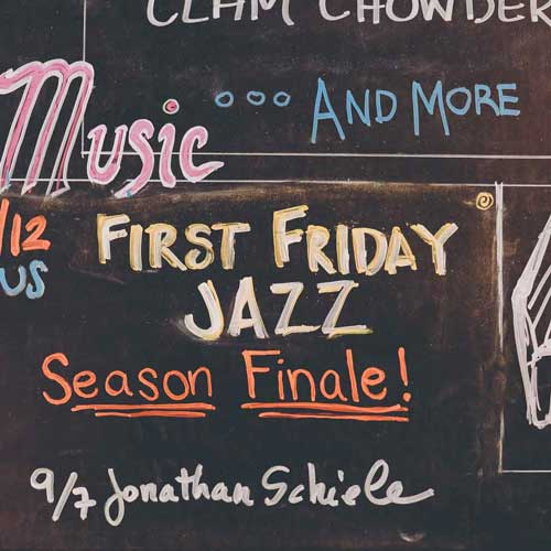 Music listing for First Friday Jazz on chalkboard.