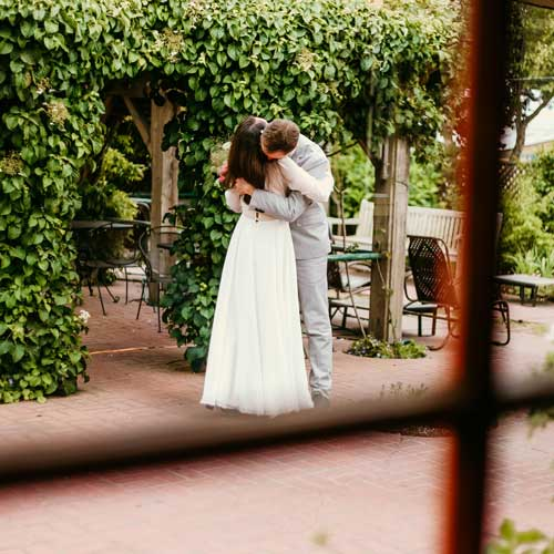 Groom and bride embracing in the garden.